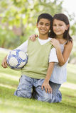 Children playing football in park Stock Image