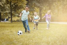 Children playing football at public park. Stock Photos
