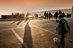 Children playing football at sunset in Naples Royalty Free Stock Image