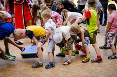 Children playing fun game pass each other box between their legs at pirate party royalty free stock image