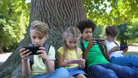 Children playing gadgets, sitting under tree in park, boy smiling in camera, app