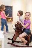 Children playing in the gameroom. Three children playing in the gameroom stock photo