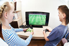 Children playing on games console to play football Stock Images
