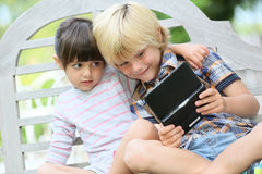 Children playing with games on outdoor bench Royalty Free Stock Photo