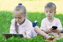 Children playing games on a tablet PC and smartphone. Brother and sister Stock Photos
