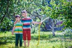 Children playing with garden sprinkler. Preschooler kids run and stock photography