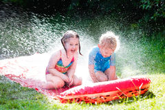 Children playing with garden water slide Royalty Free Stock Image