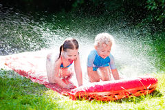 Children playing with garden water slide Royalty Free Stock Photography