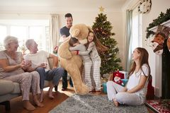 Children Playing With Giant Teddy Bear As Multi-Generation Family Open Gifts On Christmas Day stock photos
