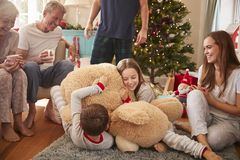 Children Playing With Giant Teddy Bear As Multi-Generation Family Open Gifts On Christmas Day royalty free stock photography