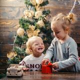 Children playing with gift. Christmas gift box and happy family. Kids opening Xmas presents. Winter evening at home stock photo