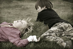 Children playing. Girl and a boy playing outside in a grassy field Royalty Free Stock Photo