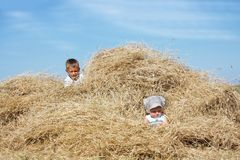 Children playing in haystack Royalty Free Stock Photo
