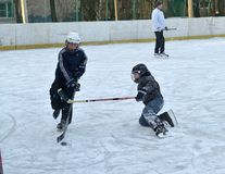 Children playing hockey on the rink. stock photo