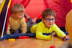 Children playing  at home. Children playing on  floor with colored toys Royalty Free Stock Photo