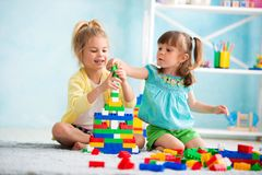 Children playing at home on the floor with cubes.  royalty free stock image