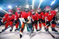 Children playing ice hockey on the rink royalty free stock photo