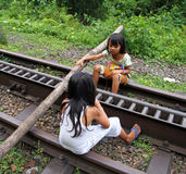 CHILDREN PLAYING IN INDONESIA. Two girls use a tree trunk on a disused railway track as a seesaw in West Sumatra, Indonesia royalty free stock images