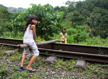 CHILDREN PLAYING IN INDONESIA. Two girls use a tree trunk on a disused railway track as a seesaw in West Sumatra, Indonesia stock photos