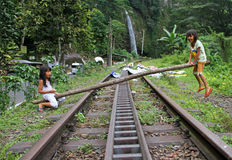 CHILDREN PLAYING IN INDONESIA. Two girls use a tree trunk on a disused railway track as a seesaw in West Sumatra, Indonesia. A waterfall can be seen in the stock image