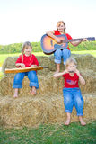 Children playing instruments. Three happy farm girls with blond braids sitting on straw bales and dressed in red shirts and blue jeans playing a guitar Stock Photo