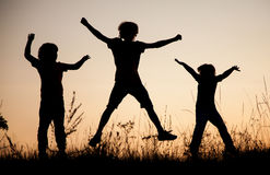 Children playing jumping on summer sunset meadow silhouetted Stock Images