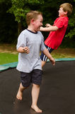 Children playing while jumping on trampoline outdoors Royalty Free Stock Image