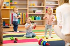 Nursery babies play on floor with carers or mothers in day care centre. Nursery babies play with carers or mothers on floor in day care centre stock image