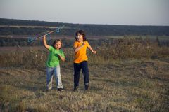Children playing kite on summer sunset meadow Royalty Free Stock Images