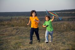 Children playing kite on summer sunset meadow Stock Image