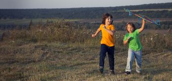 Children playing kite on summer sunset meadow.  stock photos