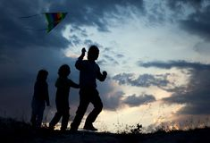 Children playing kite on summer sunset meadow silhouetted Stock Photos