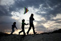 Children playing kite on summer sunset meadow silhouetted Royalty Free Stock Photography