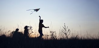 Children playing kite on summer sunset meadow silhouetted.  Stock Photos