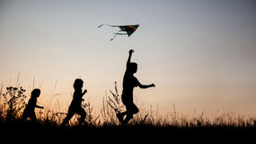 Children playing kite on summer sunset meadow silhouetted Stock Photo