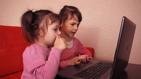 Children playing in the laptop. Two little girls are printed on a laptop. Two sisters sitting on the orange couch looking at a lap. Top. Close-up stock video