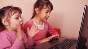 Children playing in the laptop. Two little girls are printed on a laptop. Two sisters sitting on the orange couch looking at a lap. Top. Close-up stock footage
