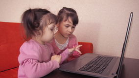 Children playing in the laptop. Two little girls are printed on a laptop. Two sisters sitting on the orange couch looking at a lap. Top. Close-up stock video footage