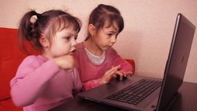 Children playing in the laptop. Two little girls are printed on a laptop. Two sisters sitting on the orange couch looking at a lap stock video