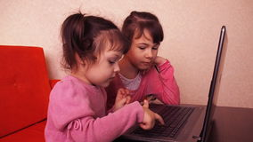 Children playing in the laptop. Two little girls are printed on a laptop. Two sisters sitting on the orange couch looking at a lap stock footage
