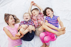 Children playing laughing tickling feet. Four children laying on blanket tickling, giggling, laughing fun Stock Images