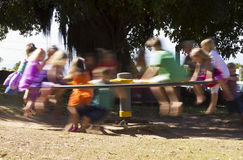 Children playing on a Merry go round Stock Image