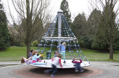 Children playing merry go round Royalty Free Stock Images