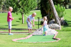 Children playing miniature golf outside. Group of happy active children, two brothers, teenage boys, and their little sister, cute toddler girl, playing Stock Photography