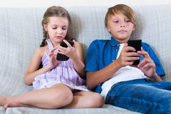 Children playing in mobile phones Royalty Free Stock Image