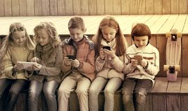 Children playing with mobile phones. Outdoor portrait of cheerful girls and boys playing with phones Stock Photo