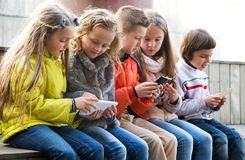 Children playing with mobile phones. Outdoor portrait of girls and little boys playing with phones. Focus on the left Stock Photo