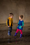 Children playing in mud. Young boy and girl playing in the mud in colorful clothes (blues, yellows, pinks and reds Stock Photos
