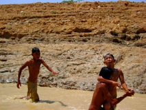 Children playing in muddy waters. Of Mekong delta royalty free stock image