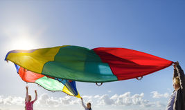 Children playing with multicolored windbreak on the beach. Stock Photos